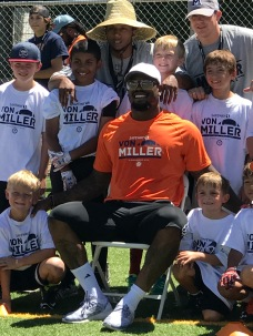 Rocco kneeling to the right of Von Miller.